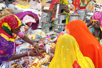 women selling bangles and other iron products in a local village market in ndia